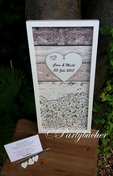Hochzeitsgästebuchrahmen mit weißen Holzherzen als Einwurf in das Gästebuch
